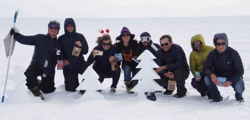 Group photo with our Christmas presents behind the trees sclupted in the ice